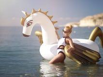 Mulher que está na praia da costa de mar perto da estância com o colchão inflável gigante do flutuador de pegasus do unicórnio no imagem de stock royalty free