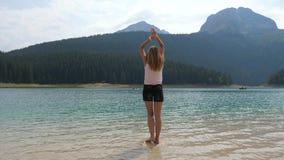 A mulher que está na rocha no lago mountain esticou suas mãos até os lados vídeos de arquivo