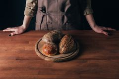 mulher que está na tabela com os loafs de pão na placa de corte de madeira Imagem de Stock