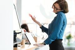 Mulher que está no café que guarda o cartão de crédito que fala pelo telefone Imagem de Stock Royalty Free