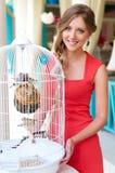 Mulher que está perto da gaiola branca com pássaros Imagem de Stock