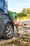 Mulher que está perto de seu carro quebrado e que olha ao motor Imagens de Stock Royalty Free