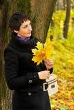 Mulher que está perto de uma árvore que guarda um ramalhete das folhas de bordo imagens de stock