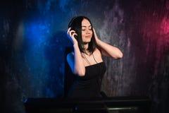 Mulher que está perto dos fones de ouvido vestindo de mistura da tabela e do computador, produzindo a música eletrônica fotos de stock