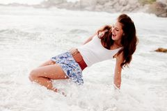 Mulher que está sendo espirrada na praia Foto de Stock