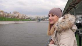 Mulher que está a uma terraplenagem do rio e que aprecia as vistas bonitas da cidade 4k vídeos de arquivo