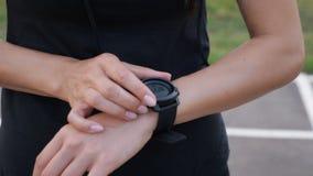 Mulher que estabelece o smartwatch da aptidão para correr Menina desportiva que verifica o dispositivo do relógio, fim acima filme