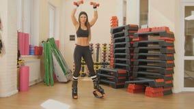 A mulher que estica em sapatas do kangoo no gym video estoque