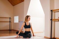 A mulher que estica a menina magro nova assentada da torção espinal faz o exercício fotografia de stock
