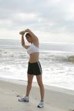 Mulher que estica na praia Fotografia de Stock Royalty Free