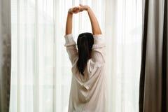 A mulher que estica no quarto após acorda, suporta a vista imagem de stock royalty free