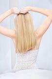 Mulher que estica os braços acima da cabeça no quarto Fotografia de Stock Royalty Free
