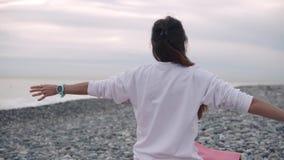 Mulher que estica os braços na praia video estoque