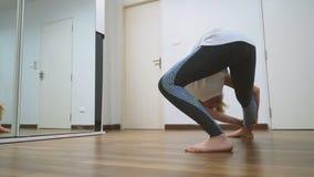 Mulher que estica perto do espelho em seu apartamento O conceito de um estilo de vida saudável, não um esporte profissional video estoque