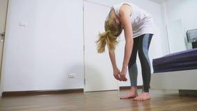 Mulher que estica perto do espelho em seu apartamento O conceito de um estilo de vida saudável, não um esporte profissional filme