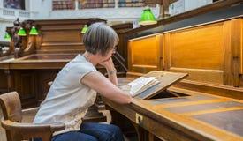 Mulher que estuda na biblioteca Fotografia de Stock Royalty Free