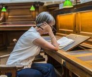 Mulher que estuda na biblioteca Imagem de Stock Royalty Free
