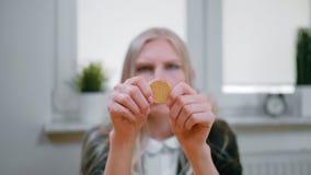 Mulher que estuda o bitcoin nas mãos Ideia do close-up das mãos da fêmea loura nova na roupa elegante que senta-se na janela e video estoque
