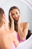 Mulher que examina sua cara olhando a no espelho