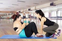 A mulher que excesso de peso fazer se senta levanta com seu instrutor Fotos de Stock Royalty Free
