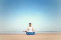 Mulher que executa exercícios do abrandamento e da meditação no mar Fotografia de Stock