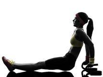 A mulher que exercita a aptidão empurra levanta com silhueta dos suportes Foto de Stock