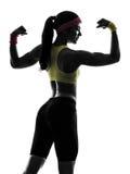 A mulher que exercita a aptidão que dobra os músculos mostra em silhueta a vista traseira Fotos de Stock