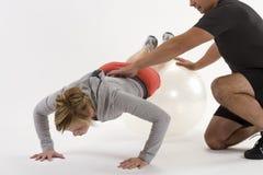 Mulher que exercita com instrutor pessoal Fotos de Stock Royalty Free