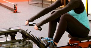 Mulher que exercita com a máquina de enfileiramento no estúdio 4k da aptidão video estoque