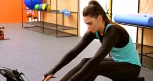 Mulher que exercita com a máquina de enfileiramento no estúdio 4k da aptidão filme