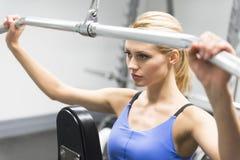 Mulher que exercita com a polia no Gym foto de stock royalty free