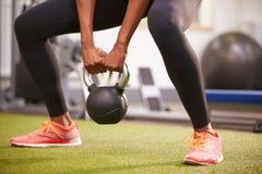 Mulher que exercita com um peso do kettlebell, colheita da baixo-seção Fotografia de Stock