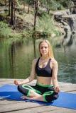 Mulher que exercita e que senta-se na posição de lótus da ioga quando medita Foto de Stock