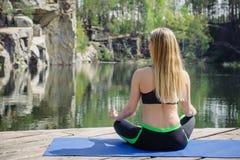 Mulher que exercita e que senta-se na posição de lótus da ioga quando medita Imagem de Stock Royalty Free