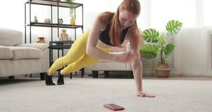 Mulher que exercita e que usa o telefone celular em casa filme