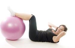 Mulher que exercita a esfera da aptidão do treinamento do núcleo Fotografia de Stock Royalty Free