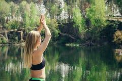 Mulher que exercita na posição da ioga ao meditar no lago Imagens de Stock