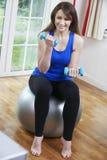 Mulher que exercita na tevê de Front Of em casa Imagens de Stock