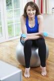 Mulher que exercita na tevê de Front Of em casa Fotografia de Stock Royalty Free