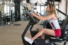 Mulher que exercita no ciclo estacionário Foto de Stock Royalty Free