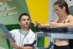 Mulher que exercita no gym com ajuda pelo instrutor pessoal imagem de stock