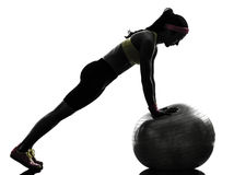 A mulher que exercita o exercício da aptidão empurra levanta a silhueta Imagens de Stock