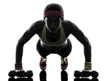 A mulher que exercita o exercício da aptidão empurra levanta a silhueta Fotografia de Stock