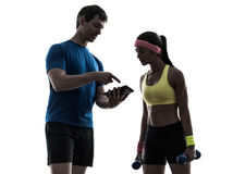 Mulher que exercita o treinador do homem da aptidão usando o silhoue digital da tabuleta fotografia de stock