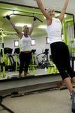 Mulher que exercita seus braços e parte traseira na ginástica em a Fotos de Stock