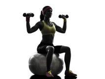 Mulher que exercita a silhueta do treinamento do peso da bola da aptidão imagem de stock