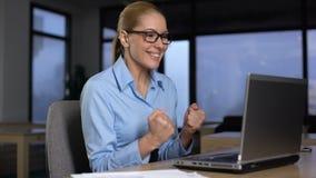 Mulher que exulta o projeto bem sucedido, lendo a boa notícia no portátil, sim gesto vídeos de arquivo