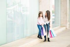 Mulher que fala à filha ao comprar imagem de stock