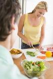 Mulher que fala ao marido ao preparar a refeição Fotografia de Stock