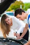Mulher que fala ao mecânico de carro na loja de reparo foto de stock royalty free